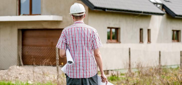 Przedsiębiorca działający w branży budowlanej stoi przodem do placu budowy, trzymając w rękach dokumenty niezbędne do zarejestrowania firmy budowlanej na terenie Niemiec