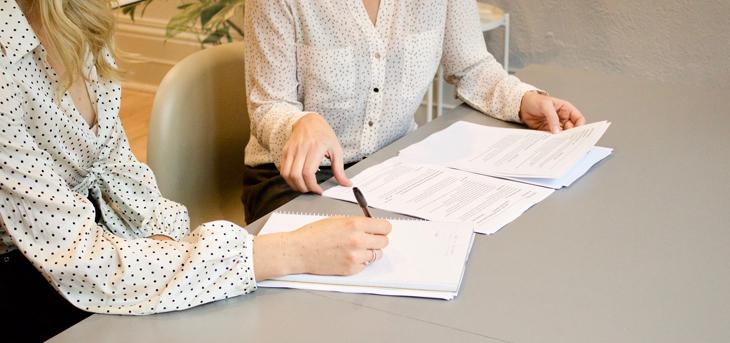 Dwie kobiety wypełniają formularze rejestracyjne potrzebne do założenia działalności gospodarczej w Niemczech